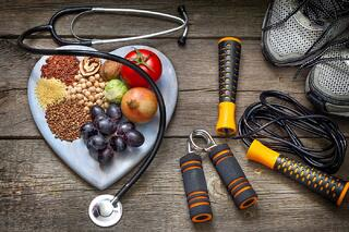 healthy foods and stethoscope with workout gear